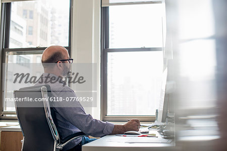 Office life. A man sitting at a desk using a computer, looking intently at the screen. Stock Photo - Premium Royalty-Free, Image code: 6118-07769529