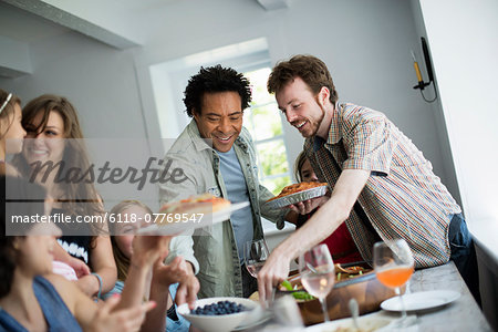 A family gathering for a meal. Adults and children around a table. Stock Photo - Premium Royalty-Free, Image code: 6118-07769547