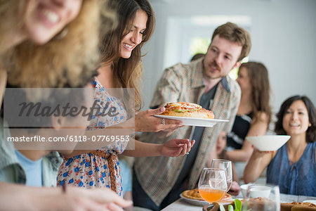 A family gathering for a meal. Adults and children around a table. Stock Photo - Premium Royalty-Free, Image code: 6118-07769553