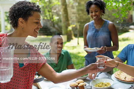 A family gathering, men, women and children around a table in a garden in summer. Stock Photo - Premium Royalty-Free, Image code: 6118-07769566