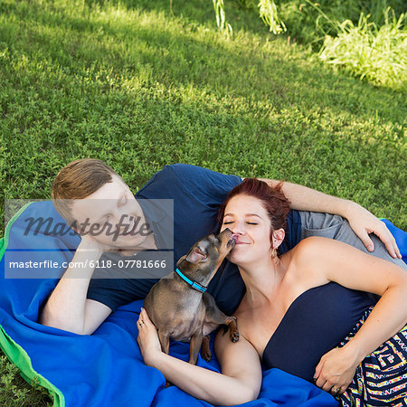 A couple sitting on a picnic rug. A small dog licking the face of a woman. Stock Photo - Premium Royalty-Free, Image code: 6118-07781666