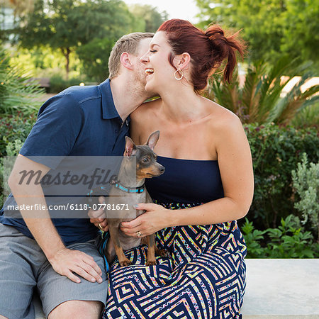 A couple playing with their small dog in the park. Stock Photo - Premium Royalty-Free, Image code: 6118-07781671