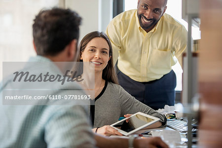 Three people in an office, two men and  a woman with computer monitor and digital tablet. Stock Photo - Premium Royalty-Free, Image code: 6118-07781693