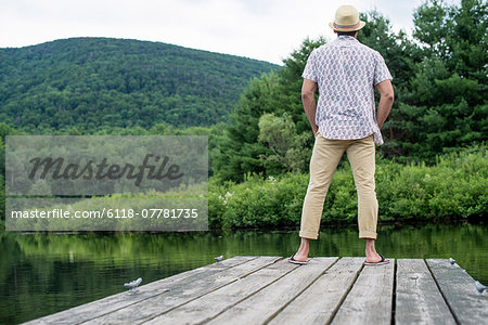 A man standing on a wooden pier overlooking a calm lake. Stock Photo - Premium Royalty-Free, Image code: 6118-07781735