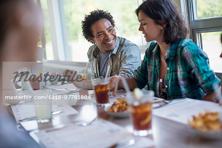 A group of friends eating at a diner. A couple seated side by side. Stock Photo - Premium Royalty-Free, Image code: 6118-07781804