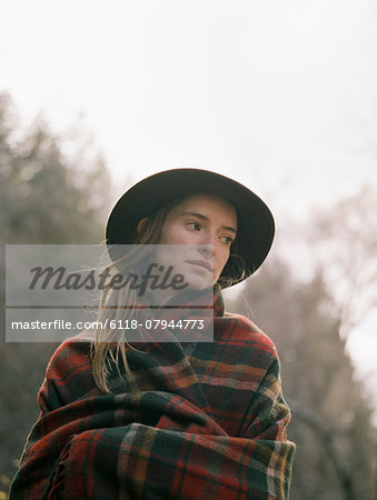 Young blond woman wearing a hat, wrapped in a blanket. Stock Photo - Premium Royalty-Free, Image code: 6118-07944773