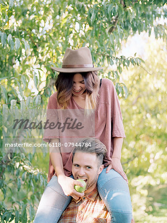 An apple orchard in Utah. man carrying a woman on his shoulders, eating an apple. Stock Photo - Premium Royalty-Free, Image code: 6118-07944784