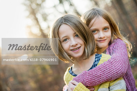 Two smiling girls in a forest, hugging each other. Stock Photo - Premium Royalty-Free, Image code: 6118-07966901