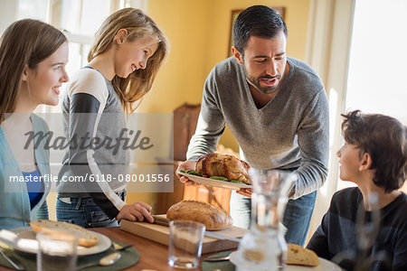 Adults and children gathered around a table for a meal. Stock Photo - Premium Royalty-Free, Image code: 6118-08001556