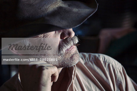 A man wearing a brimmed hat with his chin on his hand. Stock Photo - Premium Royalty-Free, Image code: 6118-08023801