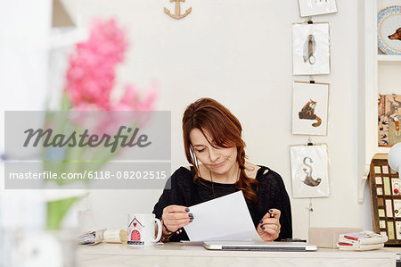 A woman sitting at a desk in a small gift shop, doing the paperwork, managing the business. A laptop on the desk. Stock Photo - Premium Royalty-Free, Image code: 6118-08202515