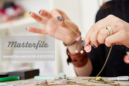 A woman seated at a workbench holding a gold chain with a small floral pendant, making jewellery. Stock Photo - Premium Royalty-Free, Image code: 6118-08202525