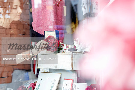 A mature woman rearranging the window display of a gift and craft store. Stock Photo - Premium Royalty-Free, Image code: 6118-08202527