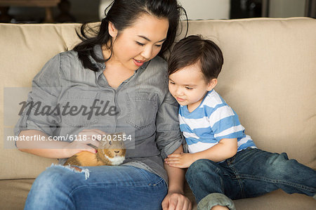 Smiling woman sitting on a sofa, a guinea pig sitting on her lap, her young son watching. Stock Photo - Premium Royalty-Free, Image code: 6118-08202554