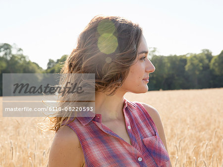 A young woman standing in a field of tall ripe corn. Stock Photo - Premium Royalty-Free, Image code: 6118-08220593