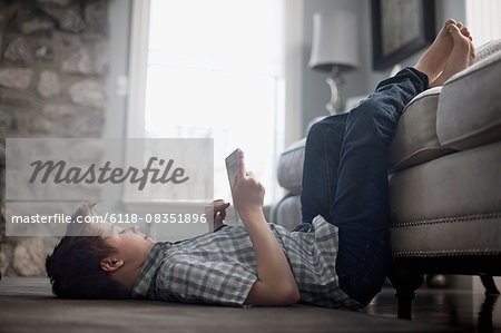 A boy lying on his back on the floor, looking at a digital tablet. Stock Photo - Premium Royalty-Free, Image code: 6118-08351896