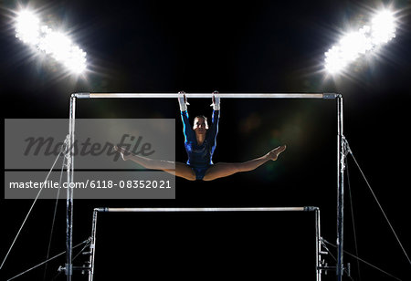 A female gymnast, a young woman performing on the parallel bars performing, with legs extended. Stock Photo - Premium Royalty-Free, Image code: 6118-08352021