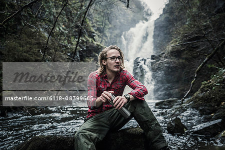 A man sitting on a rock by a waterfall, holding a flask. Winter hiking. Stock Photo - Premium Royalty-Free, Image code: 6118-08399665