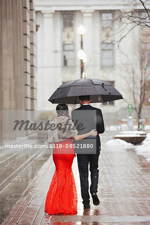 A woman in a long red evening dress with fishtail skirt and a fur stole, and a man in a suit, walking through a city. Stock Photo - Premium Royalty-Free, Image code: 6118-08521880
