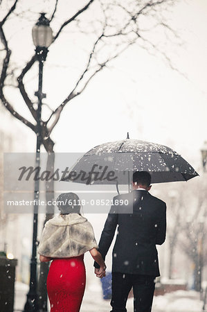 A woman in a long red evening dress and a man in a suit, walking through snow in the city. Stock Photo - Premium Royalty-Free, Image code: 6118-08521890