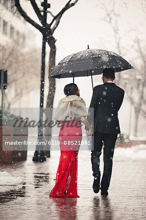 A woman in a long red evening dress with fishtail skirt and a fur stole, and a man in a suit, walking through snow in the city. Stock Photo - Premium Royalty-Free, Image code: 6118-08521891
