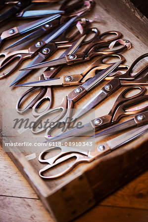 A tray of old dressmakers scissors of various sizes, some with angled blades.