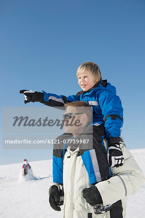 Father carrying son on shoulder, smiling, Bavaria, Germany Stock Photo - Premium Royalty-Free, Image code: 6121-07739987