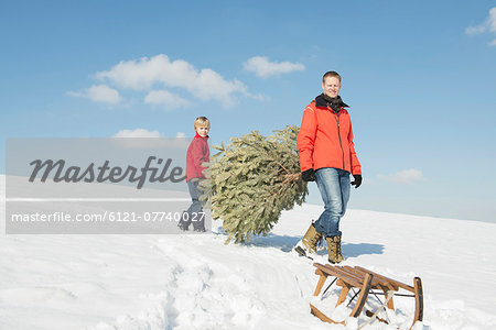 Father and son carrying spruce, Bavaria, Germany Stock Photo - Premium Royalty-Free, Image code: 6121-07740027