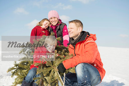 Family sitting with branches in winter, smiling, Bavaria, Germany Stock Photo - Premium Royalty-Free, Image code: 6121-07740028