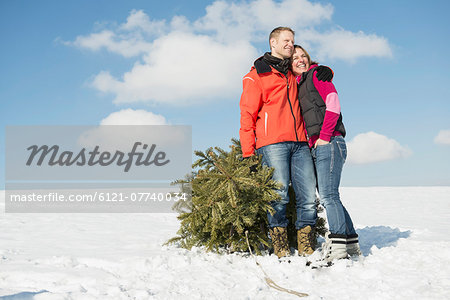 Couple standing with spruce, smiling, Bavaria, Germany Stock Photo - Premium Royalty-Free, Image code: 6121-07740034