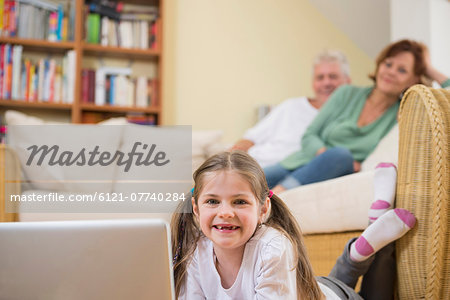Granddaughter using laptop in living room while grandparents in background Stock Photo - Premium Royalty-Free, Image code: 6121-07740284