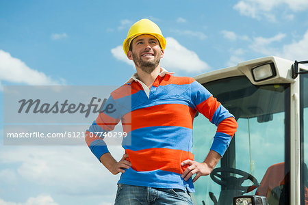 Construction worker on site with excavator Stock Photo - Premium Royalty-Free, Image code: 6121-07740299