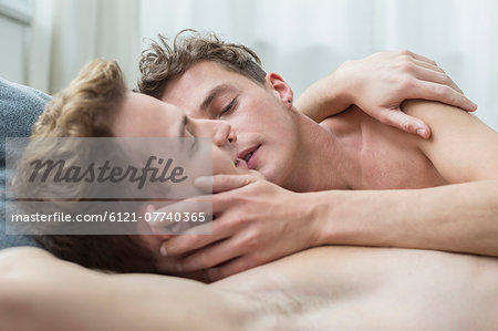 Homosexual couple caress each other in bed, close up Stock Photo - Premium Royalty-Free, Image code: 6121-07740365
