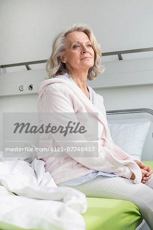 Patient in hospital sitting on bed Stock Photo - Premium Royalty-Free, Image code: 6121-07740457