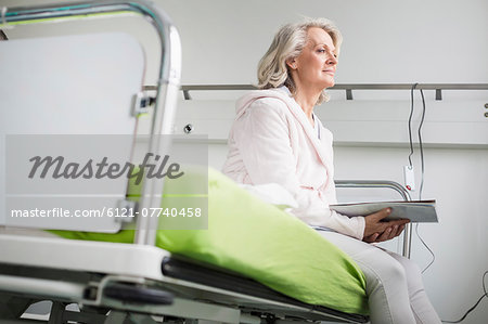 Patient in hospital sitting on bed Stock Photo - Premium Royalty-Free, Image code: 6121-07740458