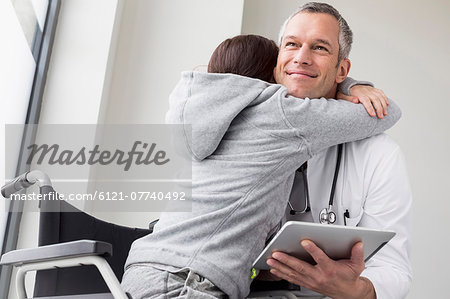 Doctor and young patient,  sitting in wheelchair Stock Photo - Premium Royalty-Free, Image code: 6121-07740492