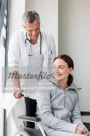Doctor and young patient,  sitting in wheelchair Stock Photo - Premium Royalty-Free, Image code: 6121-07740493