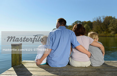 Family sitting and embracing each other on boardwalk, Bavaria, Germany Stock Photo - Premium Royalty-Free, Image code: 6121-07740501