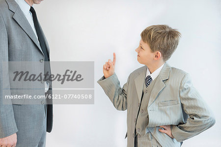 Son blusters his father against white background Stock Photo - Premium Royalty-Free, Image code: 6121-07740508