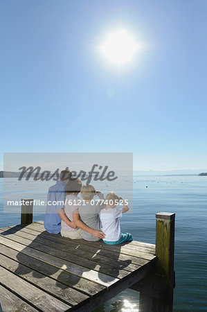 Family sitting and embracing each other on boardwalk, Bavaria, Germany Stock Photo - Premium Royalty-Free, Image code: 6121-07740525