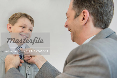 Father adjusting sons tie, smiling Stock Photo - Premium Royalty-Free, Image code: 6121-07740551