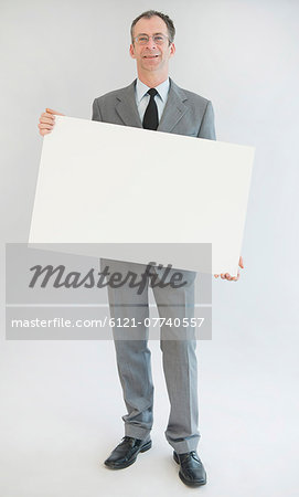 Portrait of mature man holding blank whiteboard, smiling Stock Photo - Premium Royalty-Free, Image code: 6121-07740557