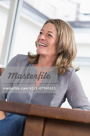 Smiling mature woman at table Stock Photo - Premium Royalty-Free, Image code: 6121-07740613