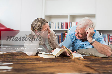 Happy couple lying on floor reading book Stock Photo - Premium Royalty-Free, Image code: 6121-07740622