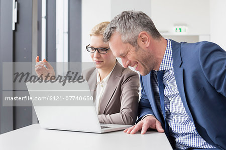 Colleagues having meeting in office, smiling Stock Photo - Premium Royalty-Free, Image code: 6121-07740650