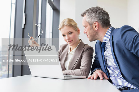 Colleagues having meeting in office, smiling Stock Photo - Premium Royalty-Free, Image code: 6121-07740651