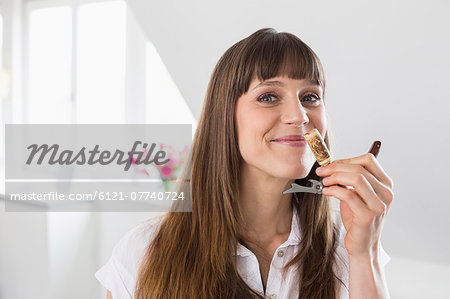 Portrait of mid adult woman smelling wine cork Stock Photo - Premium Royalty-Free, Image code: 6121-07740724
