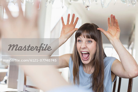 Mid adult woman making funny faces Stock Photo - Premium Royalty-Free, Image code: 6121-07740745