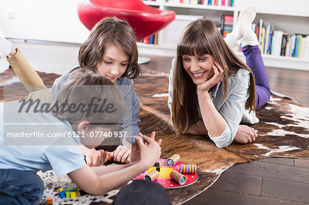 Mother playing board game with her children Stock Photo - Premium Royalty-Free, Image code: 6121-07740937
