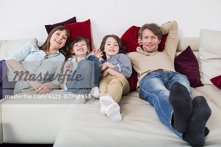 Portrait of family lying on couch, smiling Stock Photo - Premium Royalty-Free, Image code: 6121-07740953